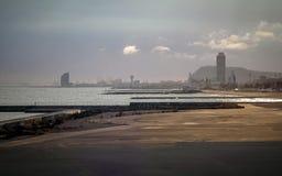 在早晨日出的巴塞罗那海滩与在的海和海湾区域 免版税库存图片