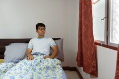 在早晨时间的亚洲人看书在床 库存照片