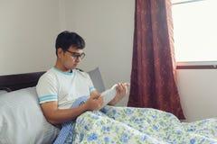在早晨时间的亚洲人看书在床 免版税库存图片