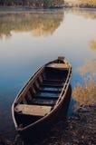 在早晨河河岸的老小船  免版税库存图片