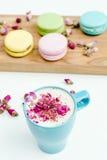 在早晨法国macarons和一个蓝色热奶咖啡杯子的看法有玫瑰花瓣的 免版税库存照片