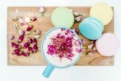 在早晨法国macarons和一个蓝色热奶咖啡杯子的顶视图有玫瑰花瓣的 免版税库存图片