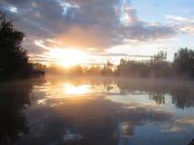 在早晨薄雾湖的日出反射 免版税库存照片