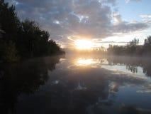 在早晨薄雾湖的日出反射 免版税库存图片