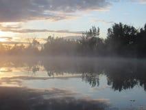 在早晨薄雾湖的日出反射 免版税图库摄影