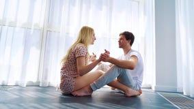 在早晨阳光下放大年轻夫妇坐地板和握手 股票视频