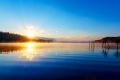 在早晨雾的美好的湖视图与神秘的山和树作为一个痣的残羹剩饭在金子,紫色-蓝色口气 免版税图库摄影
