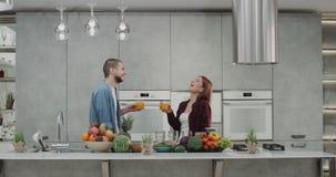 在早晨饮用的橙汁过去的美好的年轻夫妇在厨房里他们愉快微笑和有一张充分的桌  股票视频