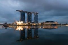 在早晨黑暗的云彩, Singapo下的现代旅馆小游艇船坞海湾沙子 免版税库存图片
