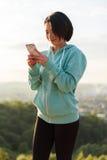在早晨锻炼期间,肉欲的年轻亚裔妇女听到在耳机的音乐 美妙的蓝天背景 库存照片