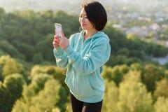 在早晨锻炼期间,运动服的肉欲的年轻亚裔妇女听到在耳机的音乐 美妙的蓝天 免版税库存照片