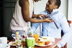 在早餐期间,黑人妻子帮助的丈夫装饰 免版税库存照片