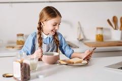 在早餐期间的聪明的热心女孩读书新闻 免版税库存图片