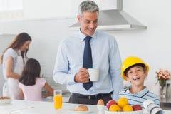在早餐期间的滑稽的小男孩佩带的父亲安全帽 库存图片