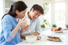 在早餐的亚洲夫妇读书报纸 免版税图库摄影