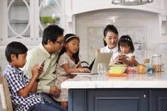 在早餐的家庭使用数字式设备 库存图片