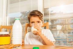 在早餐的小男孩饮用奶在厨房里 免版税图库摄影