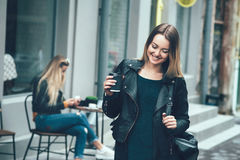 在时尚衣裳的美好的年轻时髦的偶然女服和停留在街道上和拿着黑咖啡 库存照片