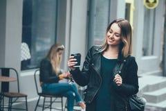在时尚衣裳的美好的年轻时髦的偶然女服和停留在街道上和拿着黑杯子 免版税库存图片
