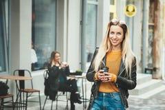 在时尚衣裳的美好的年轻欧洲女服和停留在咖啡馆前面和拿着黑咖啡, 免版税图库摄影
