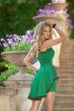 在时尚绿色礼服po的年轻美好的时兴的女孩模型 免版税库存图片