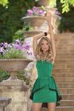 在时尚绿色礼服po的年轻美好的时兴的女孩模型 免版税库存照片