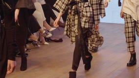 在时装期间,女性模型走跑道用不同的礼服 时尚显示新的收藏的狭小通道事件 股票录像