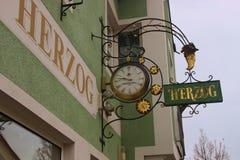 在时钟商店前面的历史的wrought-iron协会标志 温迪施加尔施滕,奥地利 库存图片