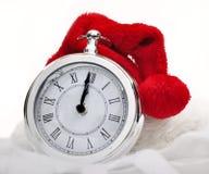 在时钟的圣诞老人帽子 库存照片