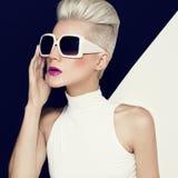 在时髦太阳镜的白肤金发的模型有时髦的理发的 方式 免版税库存照片