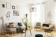在时髦客厅镶花地板上的温暖的地毯内部与时髦的扶手椅子、木咖啡桌、灰色沙发和画廊  库存照片