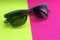 在时髦最小的多色背景的太阳镜 免版税库存照片
