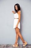 在时髦白色礼服的微笑的女性模型 免版税库存照片