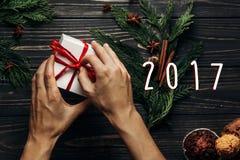 在时髦的圣诞节平的位置的2017个标志文本与手包裹 库存照片