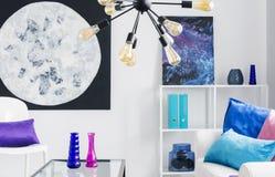 在时髦的白色客厅,真正的照片墙壁上的月亮和波斯菊图表有五颜六色的辅助部件的 库存照片