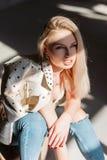 在时髦的米黄皮夹克的逗人喜爱的性感的妇女模型在有金发的葡萄酒牛仔裤有与肥满性感的嘴唇的蓝眼睛的 库存照片
