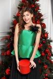 在时髦的绿色丝绸上面打扮的迷人的女孩,黑宽下摆女裙在新年树旁边摆在 免版税库存照片