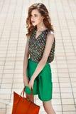在时髦的绿色短裤和一个明亮的顶面藏品橙色袋子打扮的美女在a的城市街道走 免版税库存照片