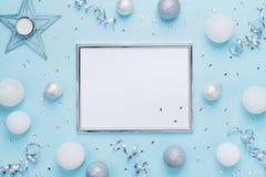 在时髦的蓝色台式视图的银色框架和圣诞节装饰 背景计算机方式模仿屏幕 平的位置 党大模型,邀请 库存照片