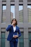 在时髦的衣服的英俊的年轻商人去他的办公室大阳台休息和有香烟 免版税库存照片