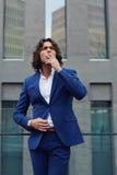 在时髦的衣服的英俊的年轻商人去他的办公室大阳台休息和有香烟 库存图片