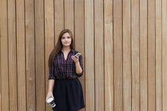 在时髦的衣裳打扮的一名年轻美丽的妇女的画象拿着手机和拿走咖啡, 免版税图库摄影