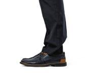 在时兴的在白色背景隔绝的鞋子和黑长裤的双人` s脚 免版税库存图片