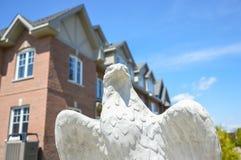 在昂贵的大厦前面的老鹰雕象 免版税库存图片