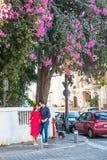 在明亮的举行手、微笑和身分的衣裳和太阳镜的浪漫夫妇在街道上的开花的树下 幸福, l 免版税库存照片