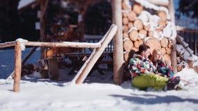 在明亮的五颜六色的滑雪服装的美好的年轻夫妇 由木存贮的可爱的夫妇和热情地坐 股票视频