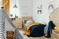 在明亮的卧室内部的时髦的木洗脸台与在墙壁上的海报 免版税库存图片