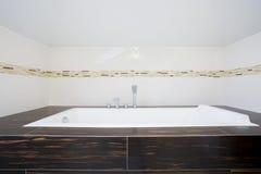在明亮的卫生间里面的方形的浴缸 免版税库存照片