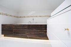 在明亮的卫生间里面的方形的浴缸 库存照片