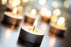 在明亮的圣诞节大气的金黄浪漫Tealights在与Bokeh -弯曲的角度的木表上 免版税库存图片